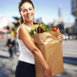 Portrait of middle aged woman carrying purchase at a crowded str — Stock Photo