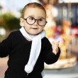 Portrait of adorable kid wearing glasses gesturing doubt against — Stock Photo