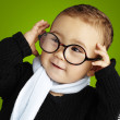Portrait of funny kid holding his glasses  against a green backg - Stock fotografie