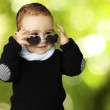 Portrait of funny kid wearing heart sunglasses against a nature — Stock Photo