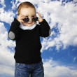 Portrait of funny kid wearing heart sunglasses against a cloudy - Zdjęcie stockowe