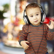 Portrait of adorable kid with headphones listening to music agai - Stock Photo