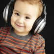 Stock Photo: Portrait of handsome kid listening to music and smiling over b