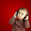 Portrait of a handsome kid listening to music looking up over re — Stock Photo