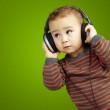 Portrait of a handsome kid listening to music looking up over gr — Stock Photo