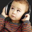 Portrait of a handsome kid listening to music looking up over bl — Stock Photo