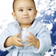 Portrait of adorable infant with blue bathrobe holding a glass w — Stock Photo