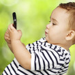 Portrait of funny kid touching mobile at park — Stockfoto