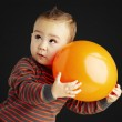 Portrait of funny kid holding a big orange balloon over black ba — Stock Photo
