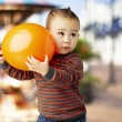Portrait of funny kid holding a big orange balloon against a car - Stock Photo