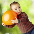 Portrait of funny kid holding a big orange balloon at park — Stock Photo
