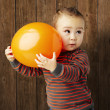 Portrait of funny kid holding a big orange balloon against a woo - 图库照片