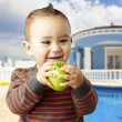 Stock Photo: Portrait of funny kid holding green apple and smiling at home