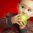 portrait of a handsome kid bitting a green apple over red backgr — Stock Photo