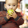 Portrait of a handsome kid bitting a green apple against a carou - Stock Photo