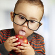 Portrait of a handsome kid wearing glasses sucking a red apple i — Stock Photo