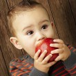 Portrait of a handsome kid sucking a red apple against a wooden — Photo