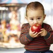 Portrait of a handsome kid sucking a red apple against a carouse — Stock Photo