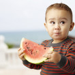 Portrait of a handsome kid holding a watermelon and tasting near — Stock Photo