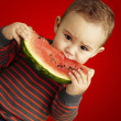 Portrait of a handsome kid holding a watermelon and sucking over - Stock Photo