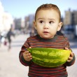 Portrait of sweet kid holding a big watermelon at city — Stock Photo