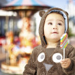 Portrait of a handsome kid wearing a brown bear sweatshirt holdi — Stock Photo #10181356