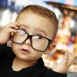 Portrait of kid wearing glasses and looking up against a carouse - Stock Photo