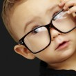 Portrait of serious kid wearing glasses and doing a gesture over — Stock Photo #10181450