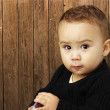 Portrait of serious kid looking ahead against a wooden wall — Stock Photo
