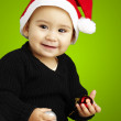 Portrait of happy kid wearing a christmas bonnet over green back - Foto Stock