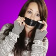 Stock Photo: Portrait of scared girl being silenced by herself over purple ba