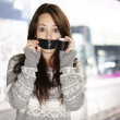Stok fotoğraf: Portrait of scared girl being silenced by herself at street