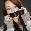 Stock Photo: Portrait of scared girl being silenced by herself over black bac