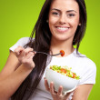 Portrait of healthy woman eating salad against a green backgroun — Stock Photo