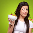 Portrait of young woman choosing pizza or salad against a green — ストック写真 #10181607