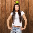 Portrait of young woman holding green apple on her head against — Stock Photo #10181629