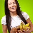 Portrait of young woman holding tropical fruits against a green — Stock Photo #10181694
