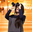 Portrait of young girl looking through a binoculars at night cit — Stock Photo