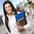 Pretty young woman smiling and holding notebooks against a stree — Stock Photo