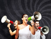 Shouting with megaphone against a grunge wall — Stock Photo