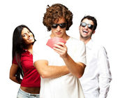 Young man playing poker with friends over white background — Stock Photo
