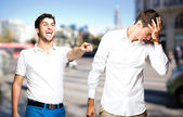Young man pointing a guy and joking at city — Stok fotoğraf