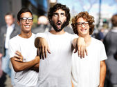 Young man joking with friends at crowded place — Stock Photo