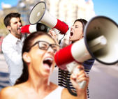 Young friends screaming with megaphone against a building — Stock Photo