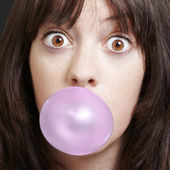 Young girl with a pink bubble of chewing gum against a black bac — Stock Photo