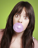 Young girl with a pink bubble of chewing gum against a green bac — Stock Photo