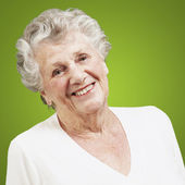 Pretty senior woman smiling against a green background — Stock Photo