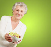 Portrait of senior woman showing a fresh salad over green backgr — Stock Photo