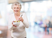 Portrait of senior woman eating salad indoor — 图库照片