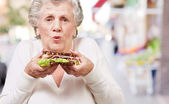 Portrait of senior woman holding a delicious sandwich at street — Stock Photo